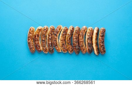 Above View With Grilled German Sausages, Alligned On A Blue Background. Authentic Grilled Nuremberge