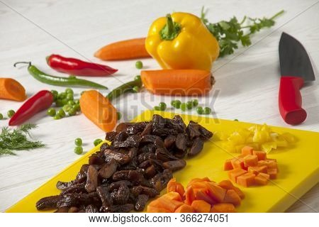 Dried And Chopped Yellow Plums. Chopped Yellow Peppers And Carrots. Yellow Chopping Board And Red Kn