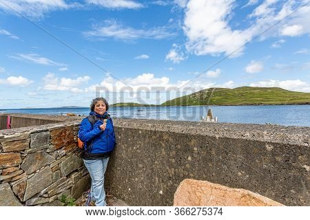 Mature Mexican Woman Savoring An Ice Cream Next To Huge Stone And Granite Fences On The Pier At Cleg
