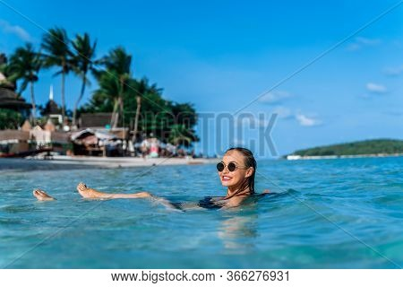 An Attractive Young Girl Is Bathing In The Calm Sea On The Beach In Clear Turquoise Sea Water. Portr
