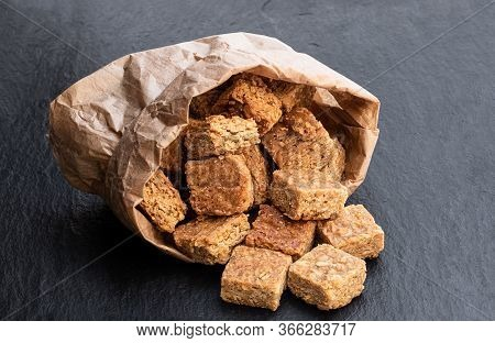 Mini  Oat And Syrup Flapjack Slices In Paper Bag On Black Stone Background