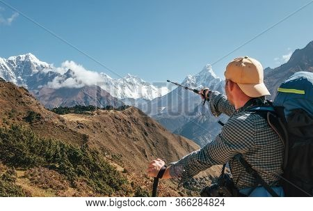 Hiker Backpacker Man Using Trekking Poles Pointing To Everest 8848m Mountain During High Altitude Ac