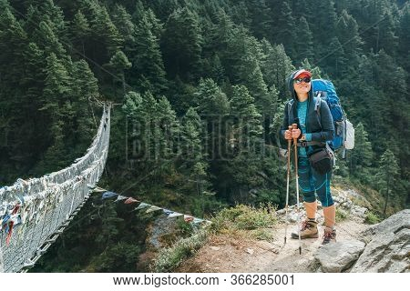 Young Smiling Female Photographer Walking Everest Base Camp Route At Canyon Over Suspension Hillary