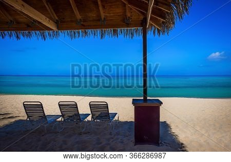 Sun Lounger Chairs Under A Hut On An Empty Seven Mile Beach In The Caribbean During Confinement, Gra