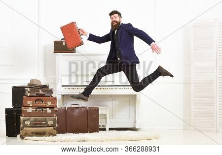 Man With Beard And Mustache In Suit Carries Luggage, Luxury White Interior Background. Macho Attract