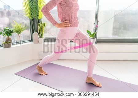 Resistance band fitness home workout woman doing lunges using loop bands for legs exercise step front and side to side exercises with strap elastic. Glute muscle activation for thighs cellulite.