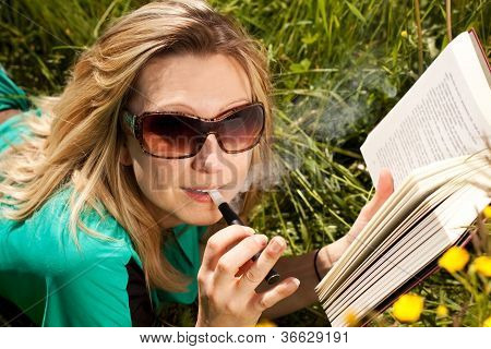 pretty blond woman reading and evaporated to an electric cigarette poster