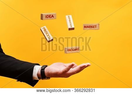 Business Startup Concept. Man Throws Wooden Blocks With Inscriptions Idea, Aspiration, Market, Proce