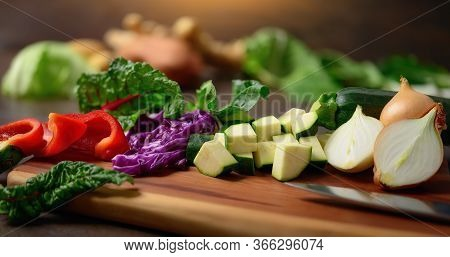 Cooking Vegetables On A Wooden Cutting Board. A Closeup With Shallow Focus Showing Colorful, Nutriti