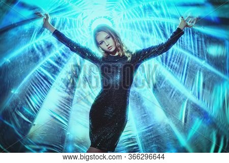 Beautiful blonde model girl in a dark sparkling dress with lurex posing in the light of softbox. Beauty, fashion.