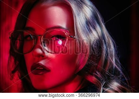 A close up portrait of a beautiful lady wearing glasses in red light. Beauty, make-up, style.
