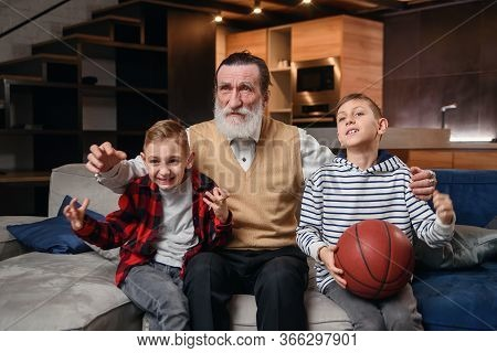 Concentrated Senior Bearded Grandpa With His Happy Grandsons Spending Their Leisure At Revision The