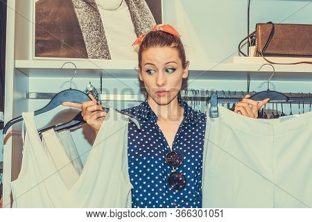 Pretty Woman Feeling Uncertain About What To Buy Choosing Deciding Between Two Outfits On Hangers In
