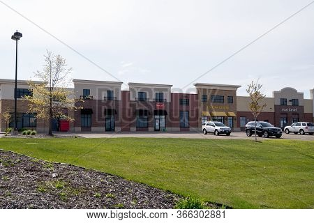 Maple Grove, Minnesota - May 14, 2020: Exterior View Of A Strip Mall Shopping Center And Parking Lot