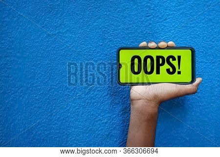 Oops Wording On Smart Phone Screen Isolated On Blue Background With Copy Space For Text. Person Hold