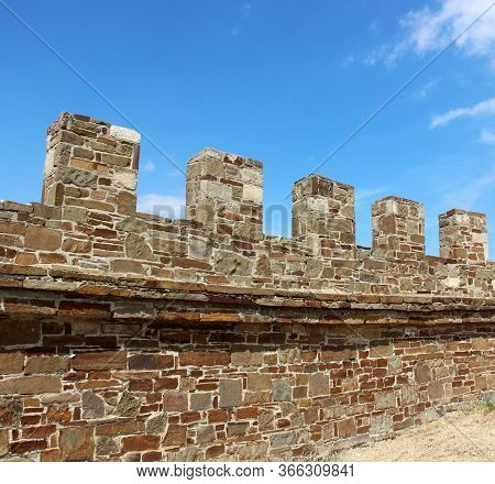 Vintage Wall With Battlements Made Of Stone And Blue Sky. Interesting Place, Ancient Architecture.