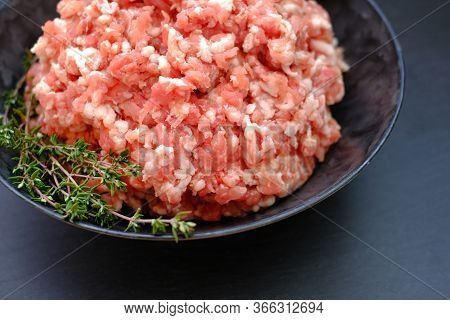 Forcemeat With Sprigs Of Thyme In A Black Cup On A Black Background.meat Food. Ground Chopped Meat A