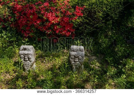 Daejeon, South Korea; May 7, 2020: Two Small Stone Carved Statues In Shade With Beautiful Red Flower