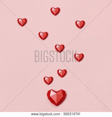 Red Polygonal Paper Hearts Shape On Cream Colored Background. Holiday Background With Copy Space For