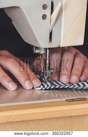 Woman Hands Using The Sewing Machine To Sew A Colorful Face Medical Mask During The Coronavirus Pand