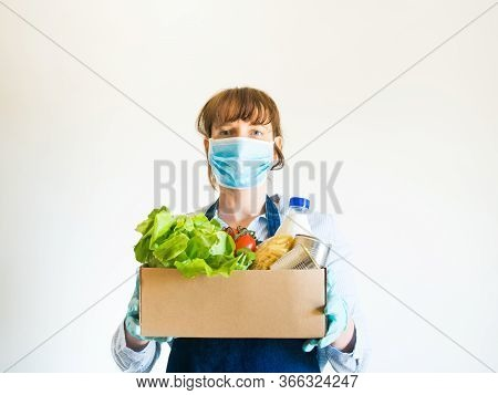 Delivery Girl Or Small Shop Owner In Blue Apron With Protective Face Mask Holding Food Delivery Box