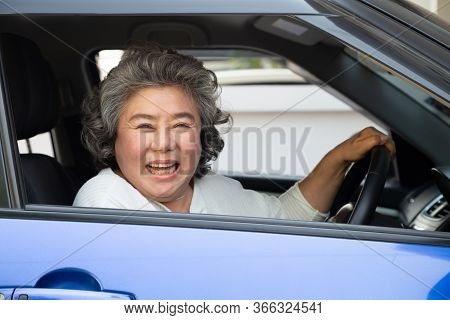 Asian Senior Woman Driving A Car And Smile Happily With Glad Positive Expression During The Drive To