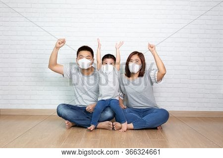 Asian Family Wearing Protective Medical Mask For Prevent Virus Covid-19 And Hand Up And Sitting Toge