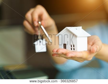 Woman Holding White House Model And House Key.concept Mortgage Loan Approval  Home Loan And Insuranc
