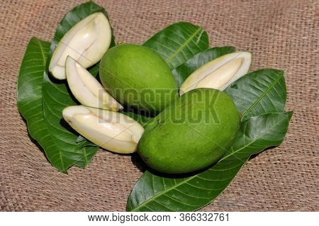 Green Mango With Mango Leaves On Burlap Background With Selective Focus