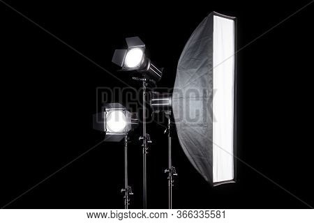 Photo Studio Lighting Stands With Flash And Softbox Isolated On The Black.