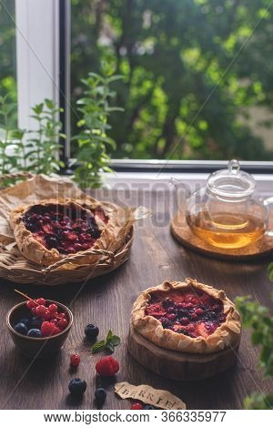 Ummer Homemade Pastry, Galette With Berries On Rustic Wooden Background