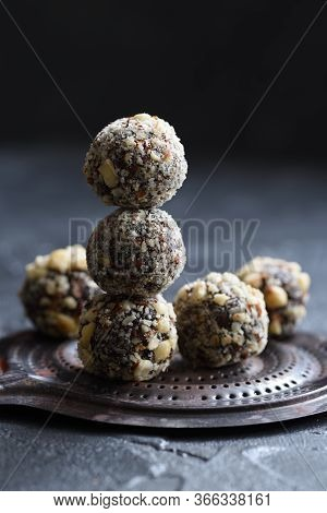 Healthy Food Concept. Homemade Coconut Energy Balls On Old Metal Tray On Black Background Angle View