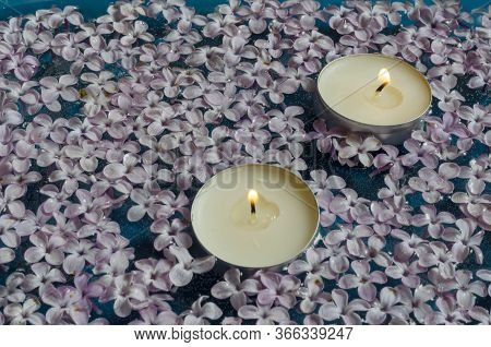 Beauty Salon, Spa, Aromatherapy Background. Candles Floating Among The Flowers Of Lilac. Two Burning