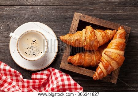 Coffee and croissants on wooden table. Breakfast meal. Top view