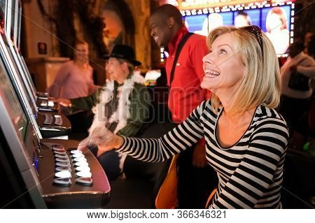 Diverse People Playing Gambling Slot Machine Game At Casino