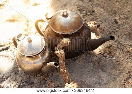 Traditional Berber Tea Cooking. Black Sooty Teapots On Bonfire In The Sahara Desert. Sun Glare On Ke