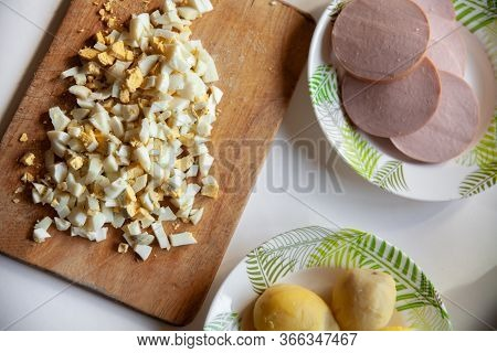 Boiled Egg, Boiled Potatoes, Boiled Sausage On A White Table