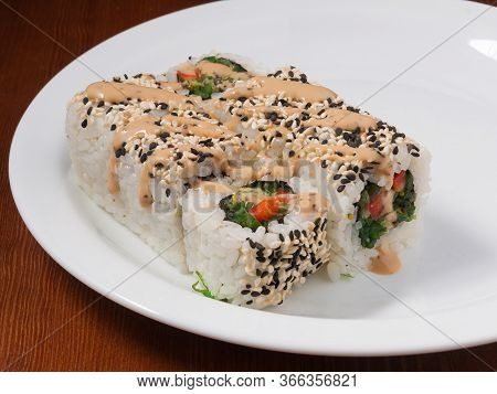Sushi Roll With Chuka Seaweed On A White Plate