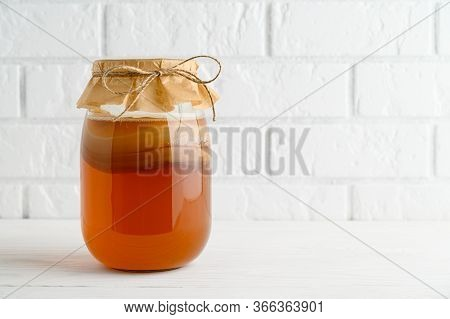 Homemade Fermented Kombucha Tea In A Glass Jar On A Background Of A White Brick Wall. Copy Space