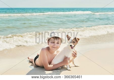 Child Boy With Dog Jack Russel On Beach. Best Friends Rest On Vacation, Play In Sand Against Sea. To