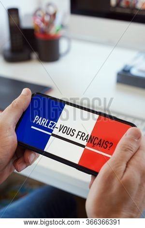 closeup of a young caucasian man, sitting at a desk, having his smartphone in his hands with the text do you speak French written in French in its screen
