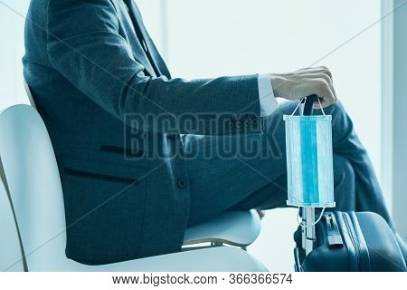 closeup of a young businessman, in a gray suit, sitting in the waiting hall of an airport or a train station, holding a surgical mask while is leaning his hand on the telescopic handle of his suitcase