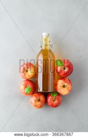 Homemade Fermented Kombucha Or Cider In A Bottle And Red Apples On A Gray Stone Background. A Health