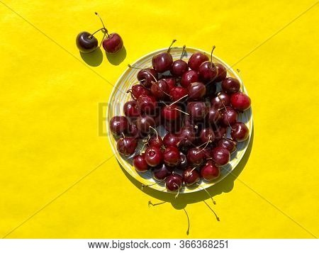 Plate Of Fresh Cherries On Yellow Background. Summer Concept
