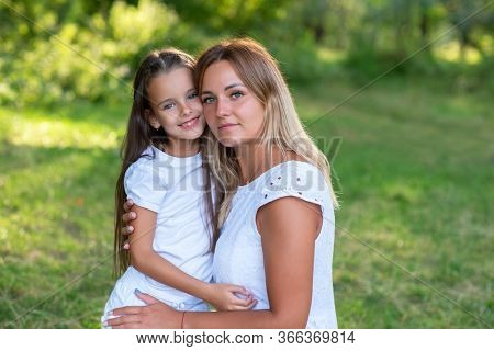 Little girl hugs her mother in summer forest nature outdoor. Portrait of mom and daughter wearing white clothes against summer greenery. Trust, kindness, maternity, parenthood, mother's love
