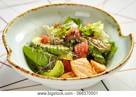 Luxury restaurant side dish top view. Salad with salmon and avocado. Fish and vegetable mix. Entree addition. Delicious meal course in deep craft plate. Fancy gourmet food closeup shot