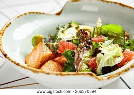 Luxury restaurant side dish top view. Salad with salmon and avocado. Fish and vegetable mix. Entree addition. Delicious meal course in deep craft plate. Fancy gourmet food overhead shot