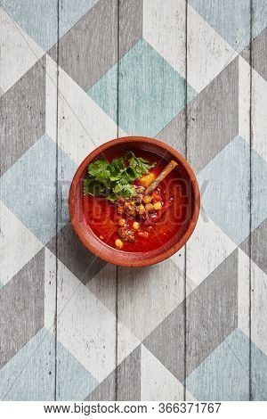 Tomato soup with mutton and chickpea top view. Restaurant dish served in brown pottery bowl. Lamb meat with tomato broth decorated with parsley. Homemade meal serving on wooden table overhead shot