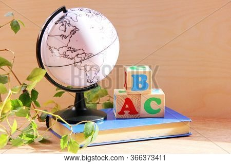 Wooden Blocks With The Letters A, B, C On A Book Next To A Globe And A Houseplant. The Concept Of Le