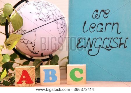 Wooden Blocks With The Letters A, B, C Next To A Globe And A Houseplant. The Concept Of Learning Eng